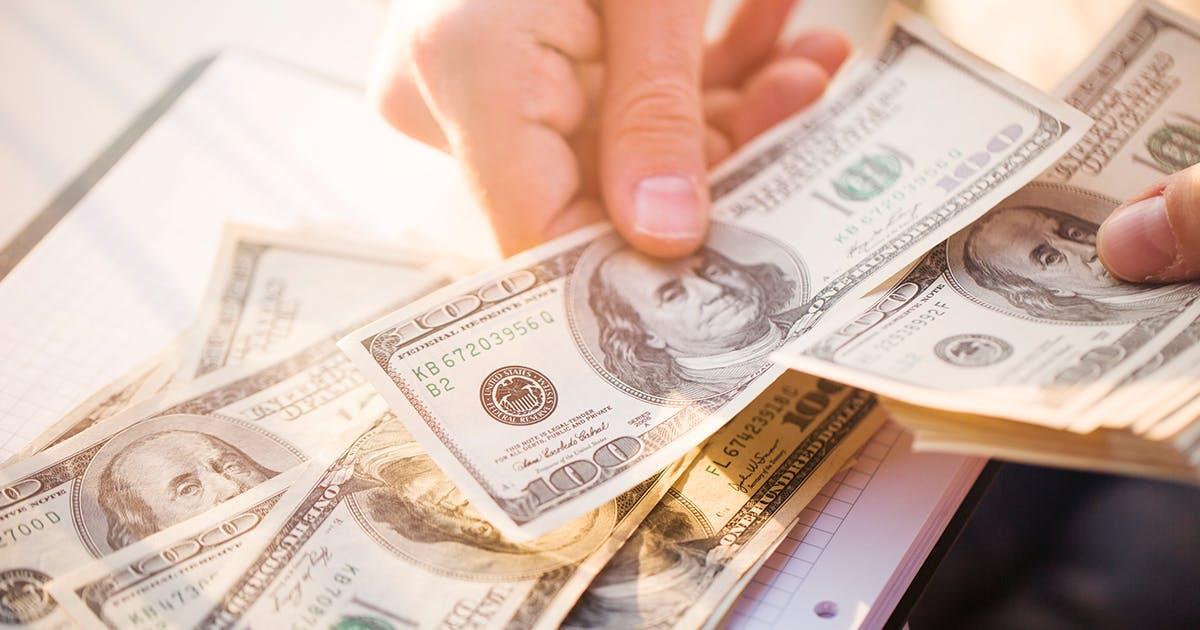 mão segura nota de dólar. Embaixo há mais notas de dólar.