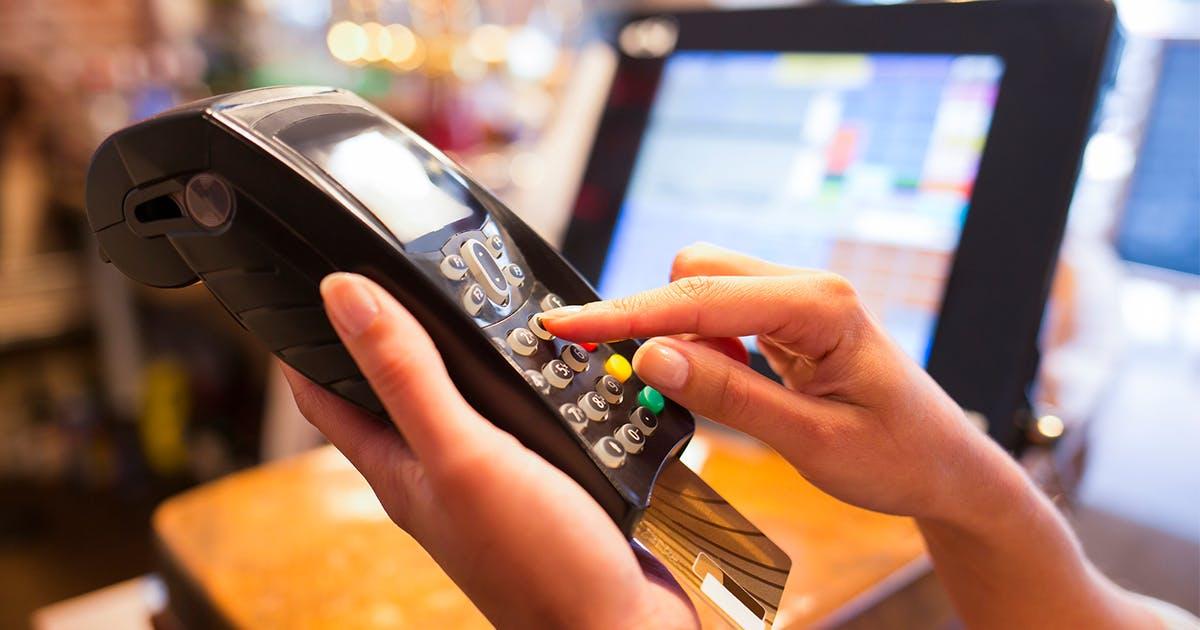 mão segura e aperta botão na máquina de cartão de crédito
