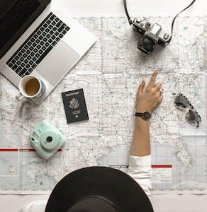 Visão aérea de uma mulher olhando um mapa e vendo quando custa um intercâmbio.