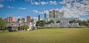 Um gramado e um castelo com o céu azul ao fundo em uma cidade do Paraguia, que é um dos países que falam espanhol.