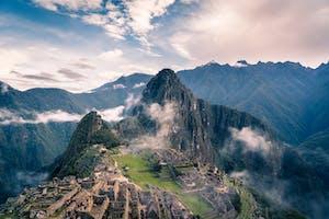 Imagem aérea de Machu Picchu, com montanhas e nuvens ao fundo.