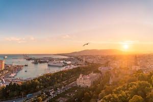 Visão aérea de um por do sol na cidade de Málaga, Espanha, com a silhueta de um pássaro voando.
