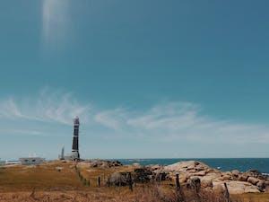 O céu azul e o farol ao fundo no Cabo Polonio, Uruguay.