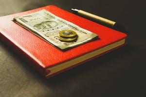 Close em moedas e notas em cima de um caderno de capa vermelha.