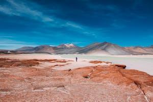 Silhueta de uma pessoa distante no deserto do Atacama, Chile.