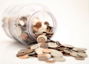 Pote de vidro cheio de moedas, representando quanto custa um intercâmbio.;