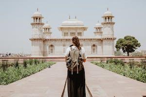 Mulher com mochila nas costas olhando para um monumento turístico após planejar e ver quanto custa um intercâmbio.
