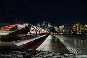 Visão noturna de um monumento com uma das melhores cidades para viver ao fundo, Calgary no Canadá.