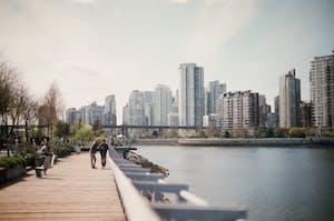 Visão de uma ponte e um lago com a cidade de Vancouver ao fundo.