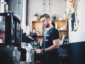 Jovem trabalhando em uma cafeteria após conquistar seu working holiday visa.