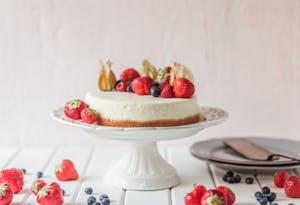 Victoria's sponge cake, uma das comidas típicas da Inglaterra, apresentada em um prato branco decorativo e frutas vermelhas.