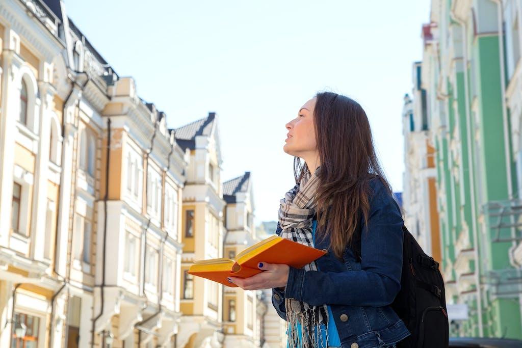 Mulher jovem, segura um livro na mão enquanto observa os prédios antigos de uma rua.