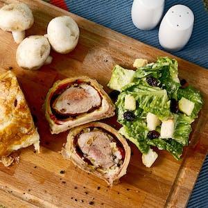 Beef Wellington, um prato típico inglês, visto de cima em uma tábua de madeira.