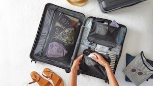 Mãos femininas organizando uma mala após entender como planejar uma viagem.