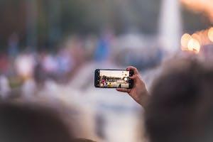 Foto com foco na tela de um celular que tira uma foto de um ponto turístico.