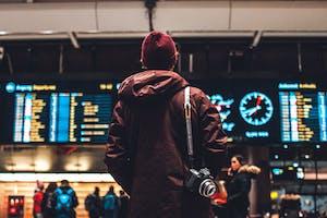 Homem de costas olhando para o itinerário de um aeroporto, após aprender como planejar uma viagem.