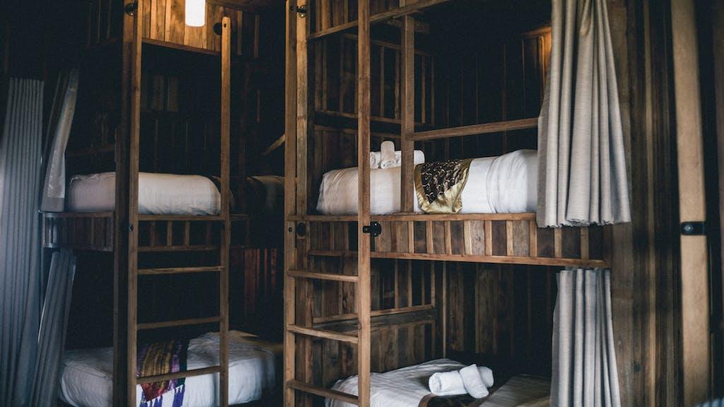 Um exemplo de o que é hostel, com camas beliche vestidas de lençóis brancos.